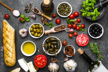 Italian food or mediterranean diet background: herbs, olive, olil, tomato, bread, cheese and wine bottle