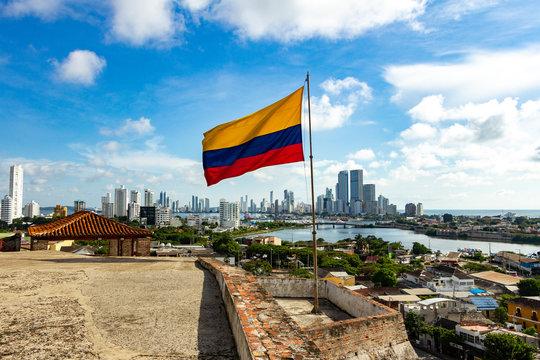 Bandera de Colombia en el Castillo de San Felipe y la ciudad moderna de Cartagena al fondo