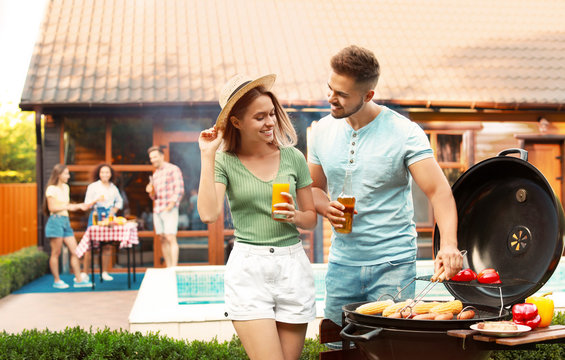 Young man and woman with drinks near barbecue grill outdoors