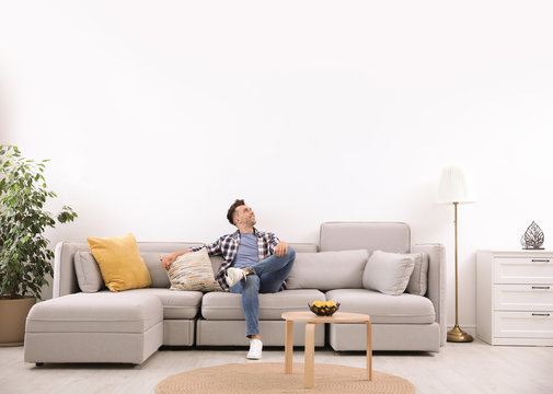 Young man relaxing on sofa under air conditioner at home