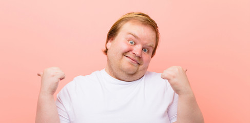 young big size man smiling joyfully and looking happy, feeling carefree and positive with both...