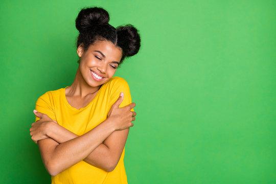 Just me myself and I. Photo of pretty dark skin lady holding herself in close hugs wear casual yellow t-shirt and red pants isolated green background