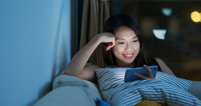 Woman watch video drama on cellphone at night
