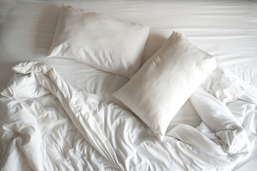 Two pillows with white blanket on messy bed.