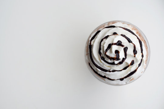 Top view of whipping cream on mocha frappe in plastic cup. Beverage background with copy space.