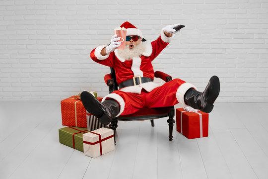 Santa Claus in armchair watching TV with popcorn in studio