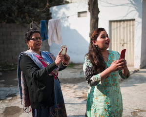 Mother and daughter in law using phones to take pictures, Punjab, Pakistan