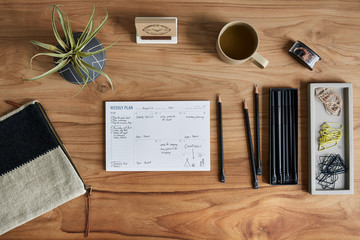 Overhead still life of a weekly calendar on a wooden desk