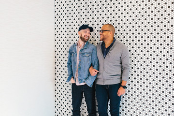 Interracial gay couple poses in front of a modern tile wall
