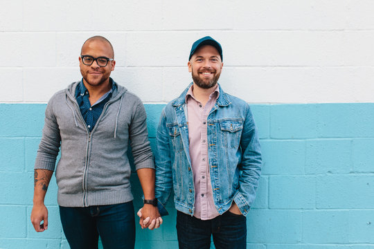 Interracial gay couple holds hands in front of a blue wall
