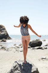 Young African American woman balancing on a rock at the ocean
