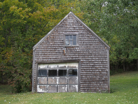 Old garage surrounded by trees and green grass