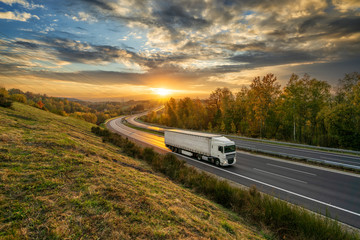 Fotobehang - White truck driving on the asphalt highway in autumn landscape at golden sunset with dramatic clouds