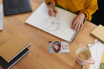 Woman at modern workspace drawing on paper
