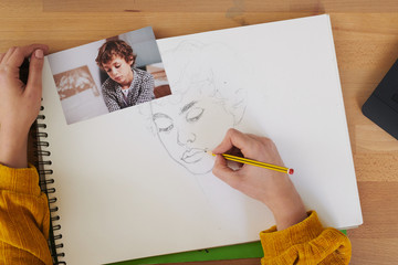 Crop woman making portrait of kid