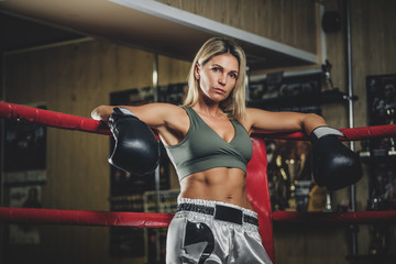 Serious blond female boxer is ready to fight, she is standing at her corner on the ring.