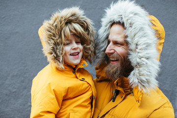 Father and kid wearing yellow hooded coat.