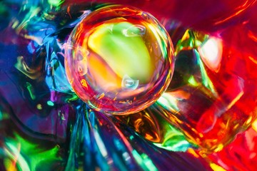 Abstract shot of glass ball on colorful holographic backdrop