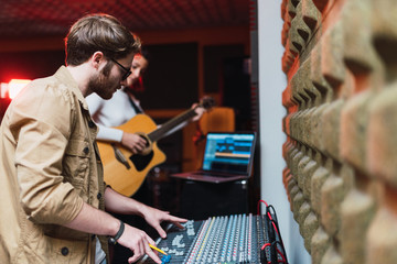 Woman playing on guitar near man using equalizer in studio