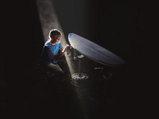 Man wearing respirator spraying paint on surfboard in dark room