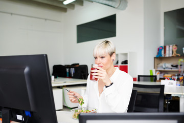 Modern businesswoman enjoying meal in office