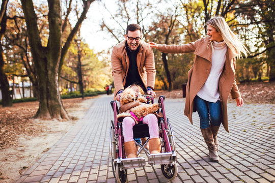 Beautiful disabled girl in wheelchair enjoying with her mother, father and dog outdoors in autumn park.