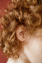 Curly hair and ear of ginger woman