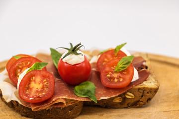 Sandwich italien sur une tranche de pain multi céréales avec une tranche de jambon rouge des tomates cerises des billes de mozzarella et du basilic frais sur une assiette en bois -isolé fond blanc