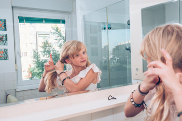 lovely blond child combing her hair in the bathroom in front of the mirror