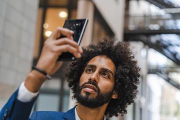 stylish black man on the street taking selfie