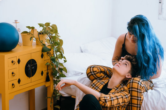 Lesbian couple dressed in a yellow outfit are comfortable in their bright white room