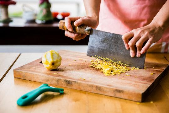 Dessert master mince lemon peel on wooden cutting board