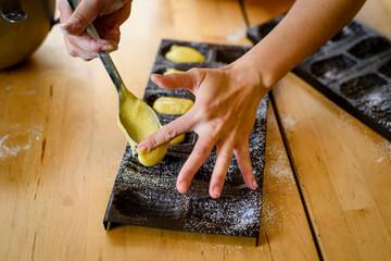 Hand put batter flowing into madeleine mold