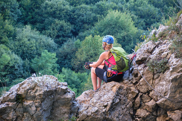 Woman sitting on rocks and admiring the view from Casa Zmeului via ferrata route in Padurea Craiului mountains, Romania, alongside Crisul Repede river.