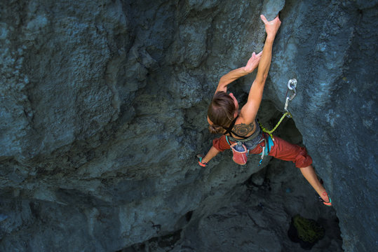 Powerful female climbing a hard overhanging wall