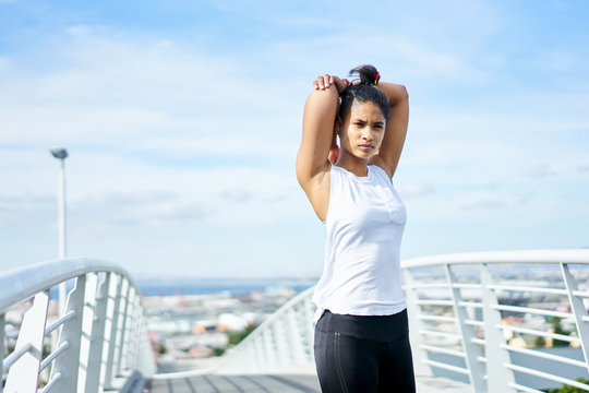 Young fit urban woman stretching whilst working out on a city walkway