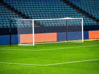 White goal post on football playing arena at empty chairs rows background