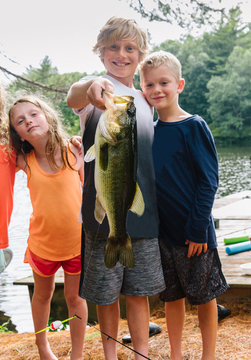 Proud Family of Kids Holding Large Fish