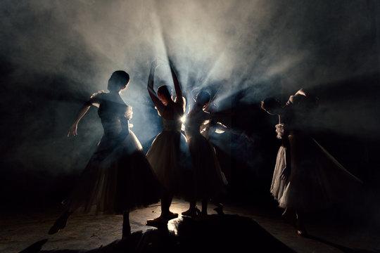 Women in dresses dancing in darkness