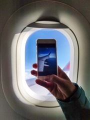 Man taking a picture through an airplane's window