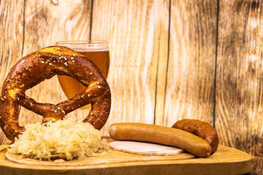 Fête de la bière (oktober fest) avec un verre de bière un bretzel géant et une choucroute garnie sur assiette en bois - fond bois clair espace pour texte ressource graphique