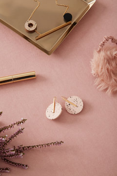 Flat lay earrings over pink table