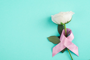 Pink ribbons with white rose on a blue background, Symbolic logo icon concept raising awareness campaign on female people living with breast cancer