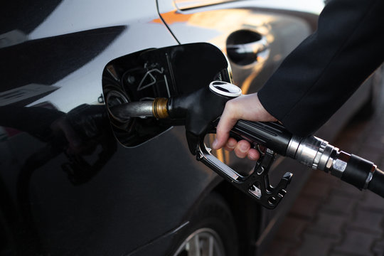 Closeup hand holding fuel nozzle to refuel oil for car in gas station
