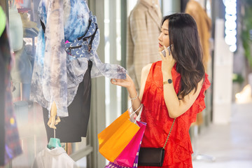 Young and beautiful Asian woman with colourful shopping bag holding her mobile phone while shopping in the shopping mall.