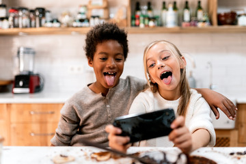 Children making faces with smartphone in kitchen