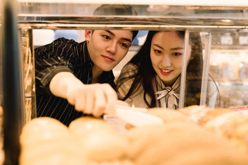 Young couple buying bakery products in store