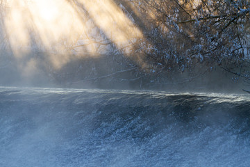 sun rays on a frosty morning near the river