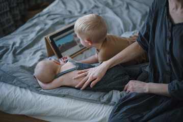 Young children play in an electronic tablet next to their mother