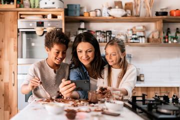 Woman with smartphone near amazed children in kitchen